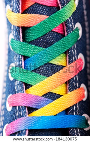 Closeup of a sneaker with colored shoelaces, abstract background