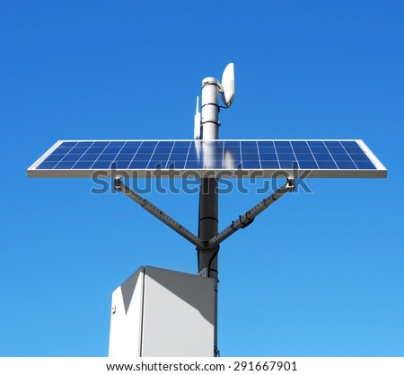 closeup of a solar panel installed in the top of a pole, over the blue sky - stock photo