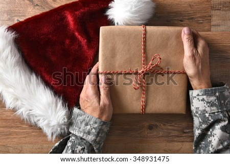 Closeup of a soldier holding a Christmas present on a wood table with a Santa hat.