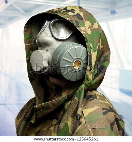 closeup of a soldier wearing a gas mask, indoor - stock photo