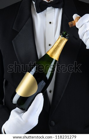Closeup of a Sommelier uncorking a champagne bottle. Man is unrecognizable wearing a tuxedo and white gloves. Vertical Format. - stock photo