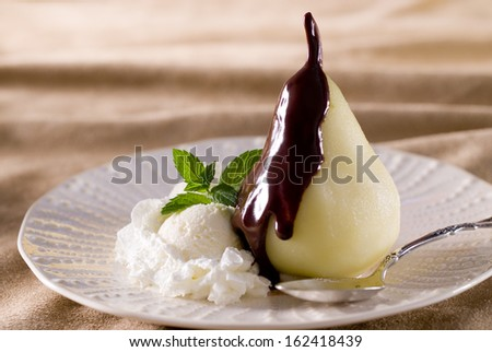 Closeup of a spiced poached pear with warm chocolate sauce and vanilla ...