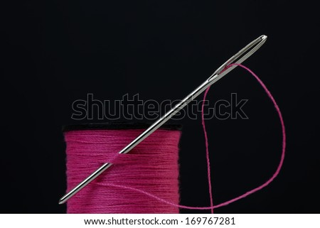 Closeup of a spool of pink sewing thread with a needle - stock photo