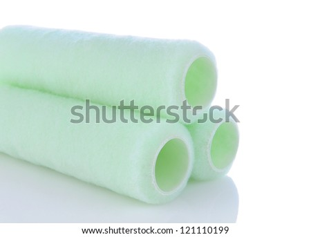 Closeup of a stack of paint roller covers on a white background with reflection. Horizontal format. - stock photo