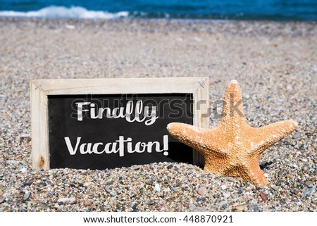 closeup of a starfish and a wooden-framed chalkboard with the text finally vacation written in it, placed on the sand of a beach