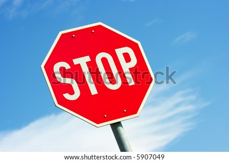 Closeup of a stop sign against clear blue sky - stock photo