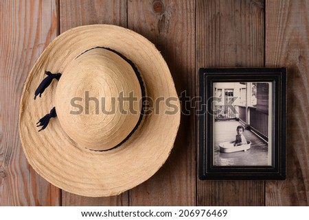 Closeup of a straw hat and a framed baby picture on a rustic wooden wall. Image can easily be replaced to insert your own.