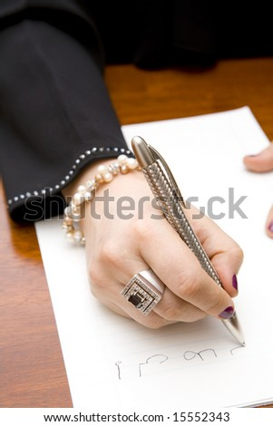 Closeup of a stylish woman writing a note in Arabic - stock photo