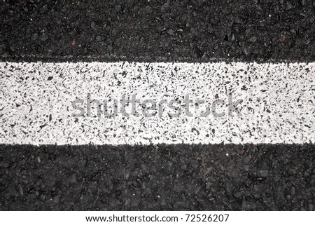 Closeup of a tar or asphalt pavement texture with a white line painted down the center. - stock photo