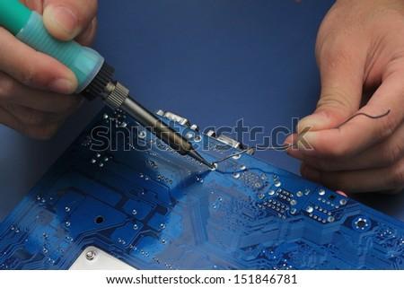 Closeup of a technician's hands soldering a computer mainboard - stock photo