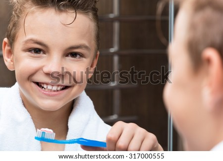 Closeup of a teen boy in the bathroom brushing his teeth - stock photo