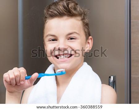 Closeup of a teen boy in the bathroom brushing his teeth - stock photo