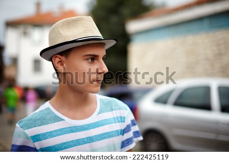Closeup of a teenager with hat in an old town, with selective focus - stock photo