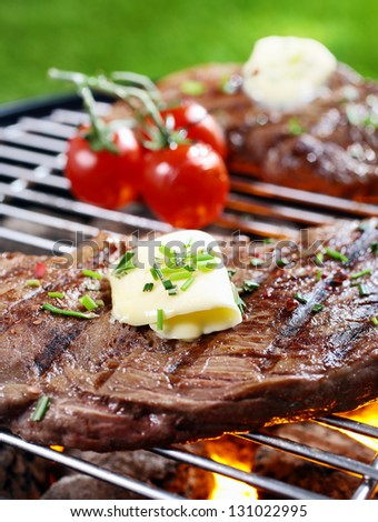 Closeup of a tender succulent portion of steak seasoned with butter and herbs grilling over a fire in a portable barbecue on a lawn - stock photo