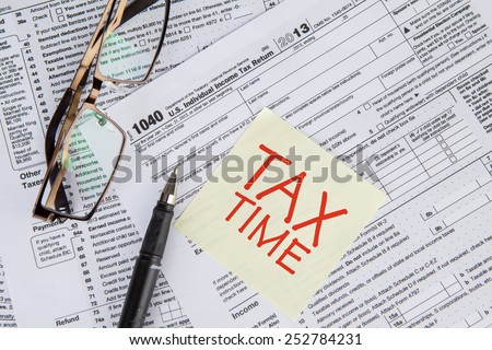 CLoseup of a text of tax time on the paper note with tax form, glasses, and pen - stock photo