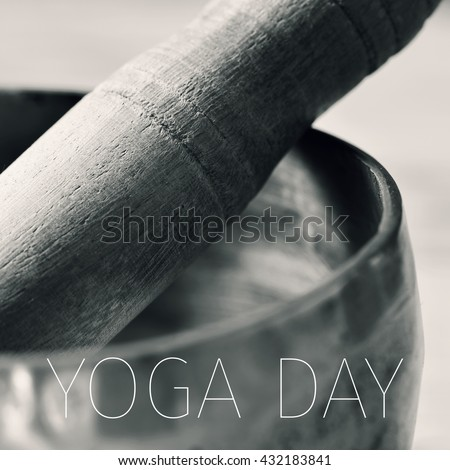 closeup of a tibetan singing bowl with its wooden mallet, in duotone, and the text yoga day - stock photo