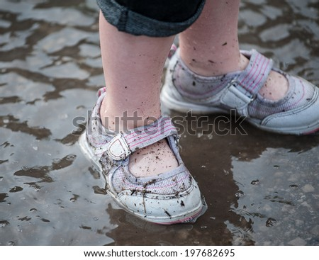 Closeup of a toddler's dirty shoes in a rain puddle, selective focus on the the debris on the right foot - stock photo