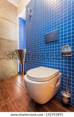 Closeup of a toilet in a modern blue bathroom with chrome basin. - stock photo
