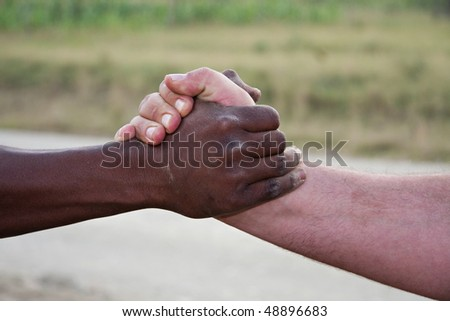 closeup of a traditional african  hand shake,interracial between black and white. Dusty,dirty hands outdoors, - stock photo