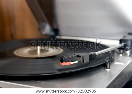 Closeup of a turntable playing a vinyl record - stock photo