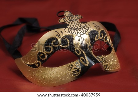 Closeup of a venetian mask commonly used in theatrical plays shot on red