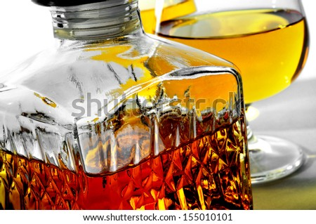 closeup of a vintage glass liquor bottle and some cognac glasses with liquor - stock photo