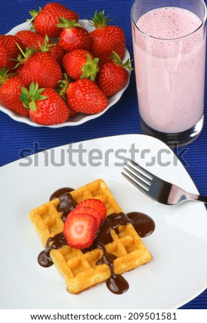 Closeup of a waffle with strawberry and chocolate sauce served on a white porcelain plate with fork over a dark blue tablecloth and a strawberry milkshake. - stock photo