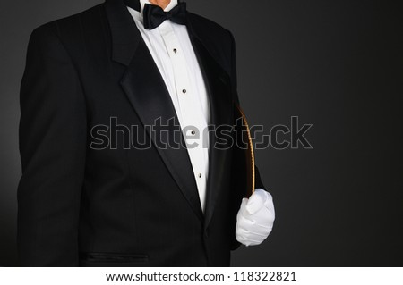 Closeup of a waiter in a tuxedo holding a serving tray under his arm. Horizontal format on a light to dark gray background. Man is unrecognizable. - stock photo
