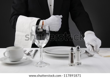 Closeup of a waiter in a tuxedo setting a formal dinner table. Shallow depth of field in horizontal format on a light to dark gray background. Man is unrecognizable. - stock photo
