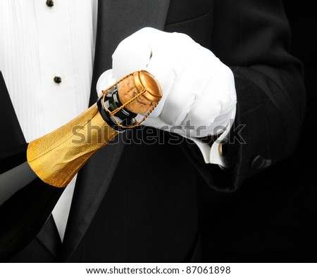 Closeup of a waiter wearing a tuxedo opening a bottle of champagne. Hand bottle and torso only. Man is unrecognizable. - stock photo