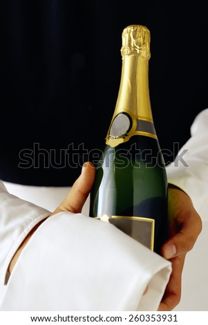 Closeup of a waiter with a bottle and flue of champagne - stock photo