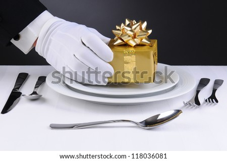 Closeup of a waiters gloved hand placing a wrapped present on the plate of a format place setting. Horizontal format with a light to dark gray background. - stock photo