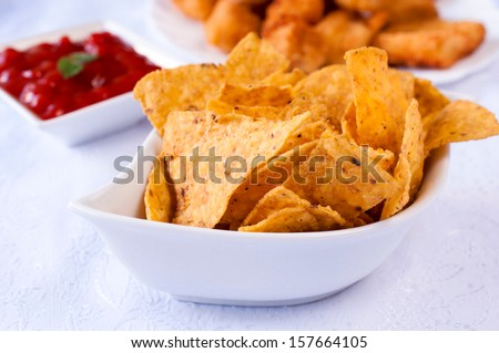 Closeup of a white bowl with nachos served as appetizer - stock photo