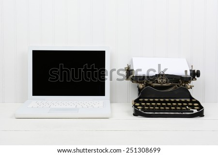 Closeup of a white desk with a modern laptop computer and an antique typewriter. Horizontal format with copy space. Old vs new concept. - stock photo