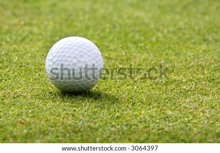 Closeup of a white golf ball on a green.  Shallow focus.
