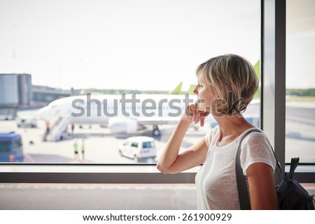 Closeup of a woman at the airport window looking to the airplane - stock photo