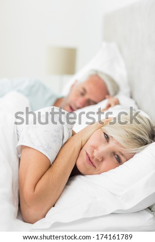 Closeup of a woman covering ears while man snoring in bed at home - stock photo