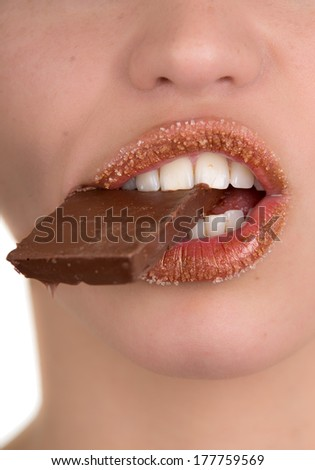 Closeup of a woman eating chocolate - stock photo