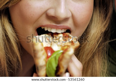 closeup of a woman eating pizza