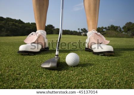 Closeup of a woman golfer about to make a putt. Horizontal shot. - stock photo