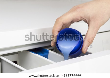 closeup of a woman  hand pouring liquid detergent in the washing machine - stock photo