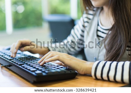 Closeup of a woman hands busy typing on a laptop. - stock photo