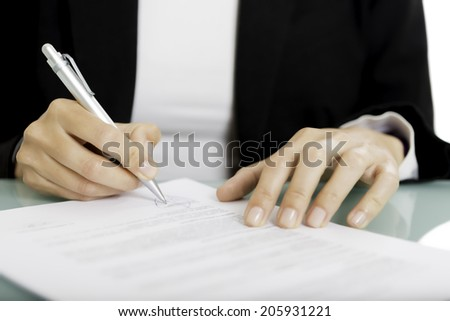 closeup of a woman hands signing a document - focus on the right hand and the pen - stock photo