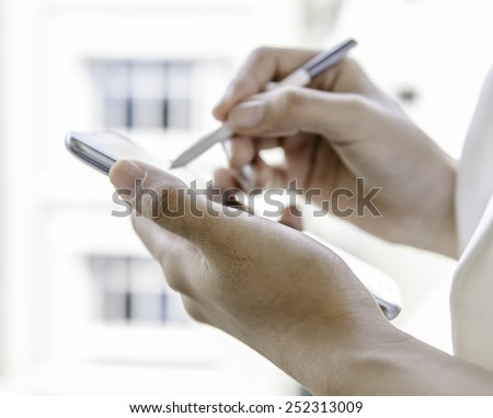 Closeup of a woman hands using tablet with stylus pen