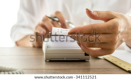 Closeup of a woman holding a printout receipt as it comes out of adding machine while she uses it to make calculations. - stock photo