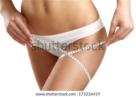 Closeup of a woman measuring her legs on white - stock photo