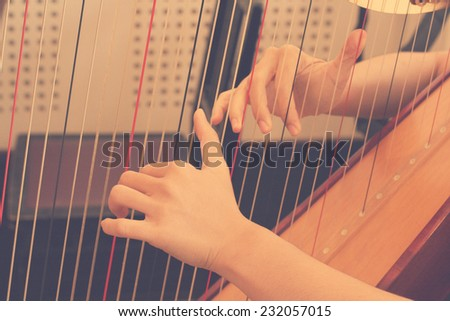 Closeup of a woman playing the harp in rehearsal practice room with retro filter effect lighting or instagram filter