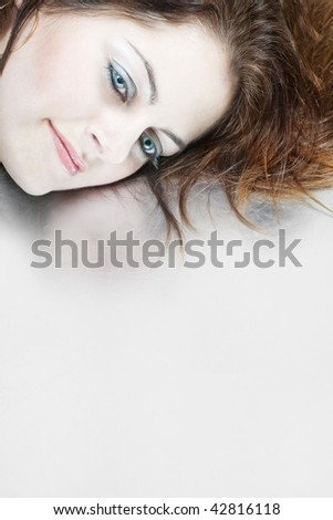 Closeup of a woman's face with blue eyes against grey background with copy space