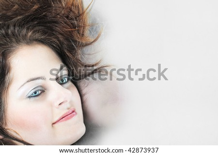 Closeup of a woman's face with blue eyes against grey background with copy space - stock photo