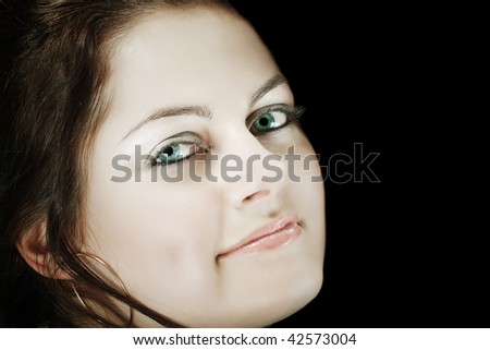 Closeup of a woman's face with emerald green eyes against black background with copy space - stock photo